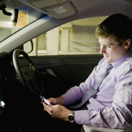 Caucasian businessman using mobile phone in car