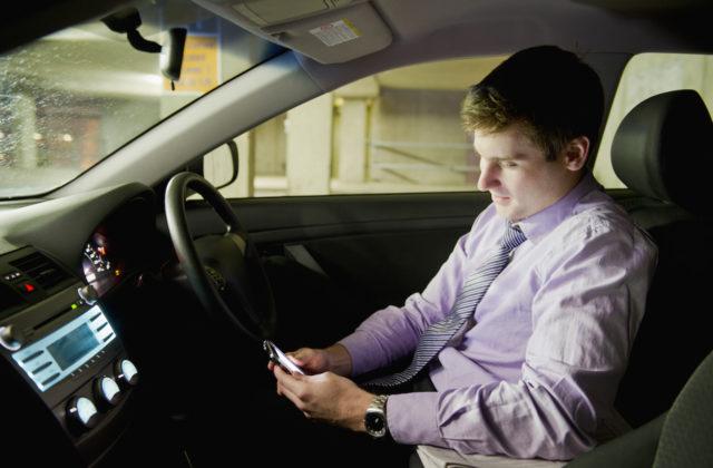 Caucasian businessman using mobile phone in car