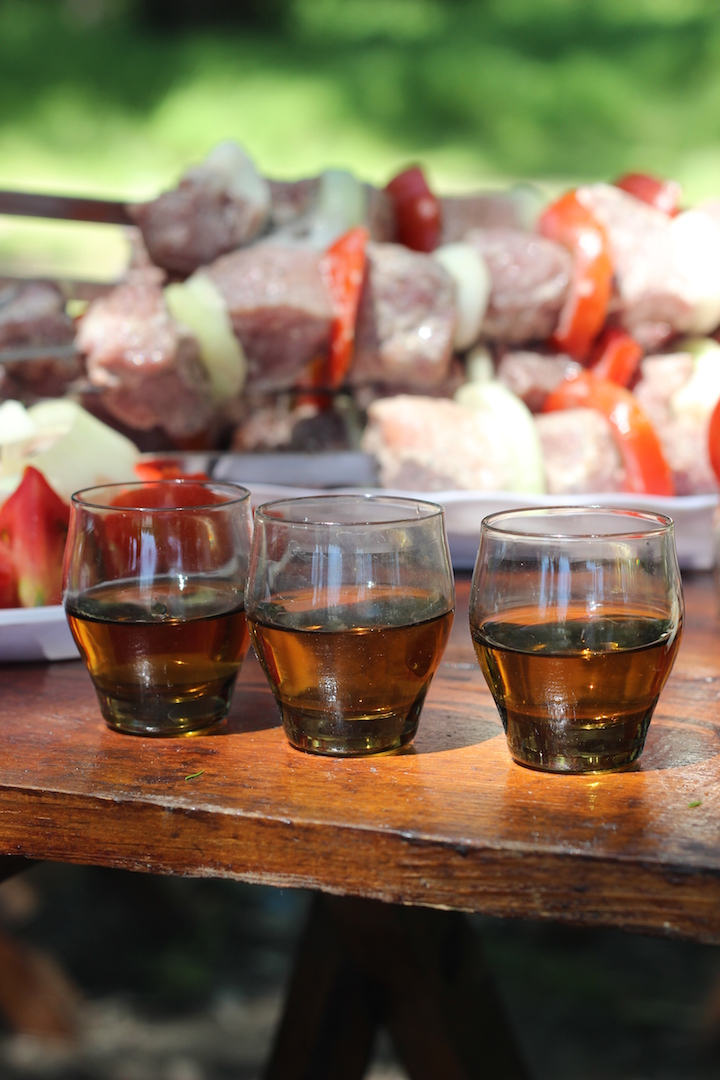 Three glasses of cognac on wooden table the background of raw kebabs threaded onto skewers