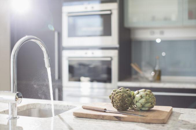 Artichokes on cutting board in modern domestic kitchen