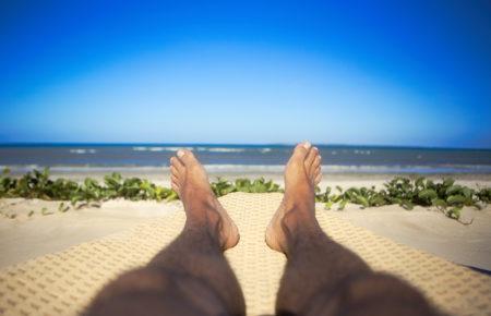 Man tanned foot legs on beach