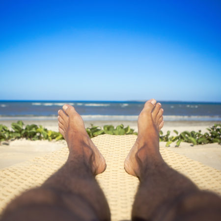 Man tanned foot legs on beach