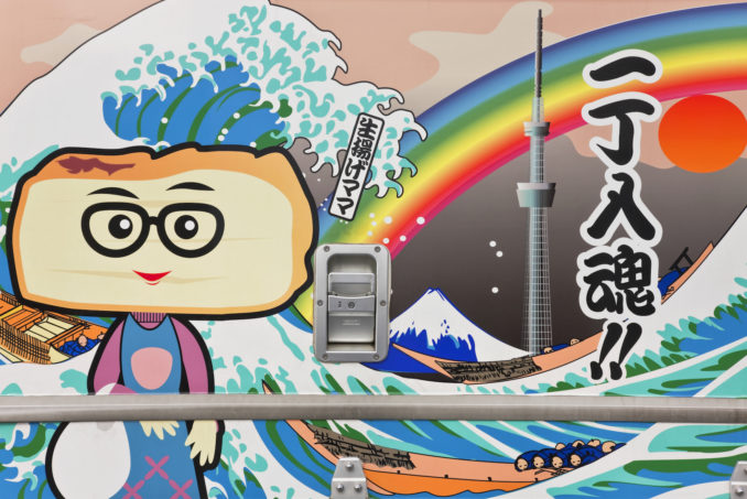 A detailed view shows an updated traditional mural with the famous Hokusai wave (Katsushika Hokusai, the renowned Edo period Japanese artist was born nearby) that also includes Tokyo Sky Tree (the world's tallest free-standing broadcast tower at 634 meters built nearby), on the side of a tofu delivery truck in the Kyojima district of Sumida Ward in the old downtown shitamachi area of Tokyo, Japan.