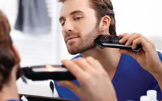 man shaving with the philips series 7000 vacuum beard trimmer