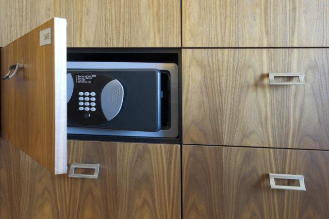 Open cabinet revealing a black safe