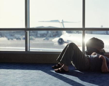 Man lying on floor in airport departure lounge