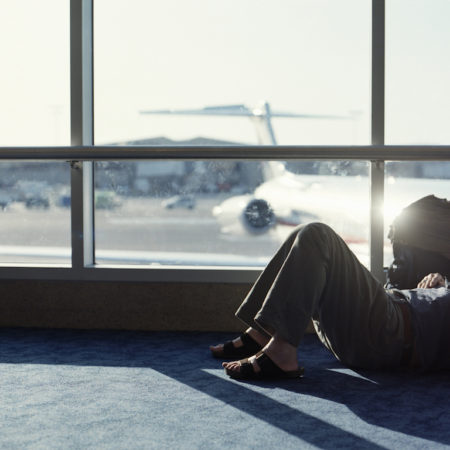 Man lying on floor in airport departure lounge