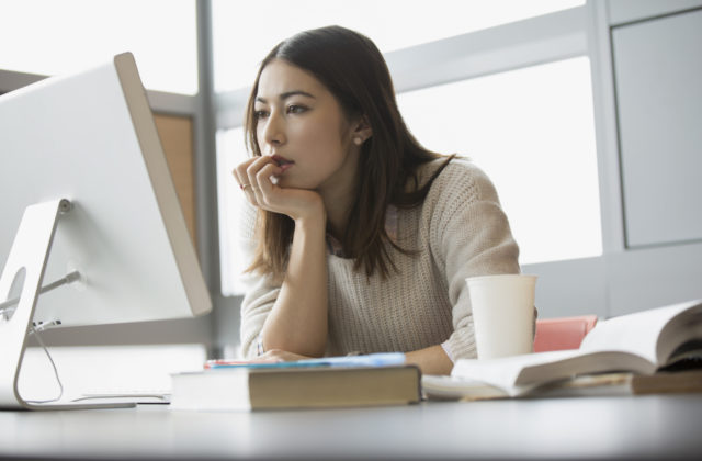 Focused college student studying at computer