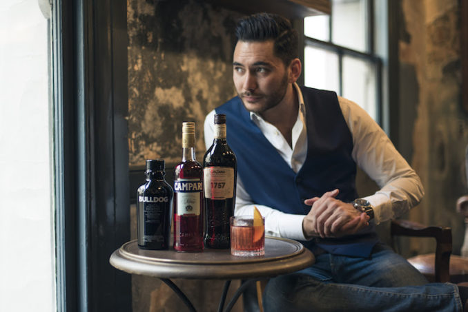 Man drinking Negroni cocktail