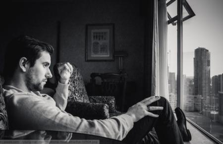 Man window sitting couch black white