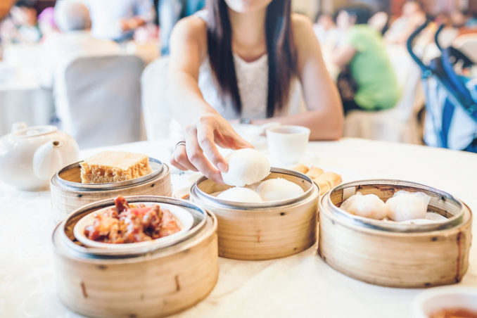 Woman enjoying a fresh steamed bun and a variety of Chinese traditional dim sum in restaurant.