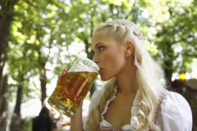 Woman drinking mug of beer outdoors
