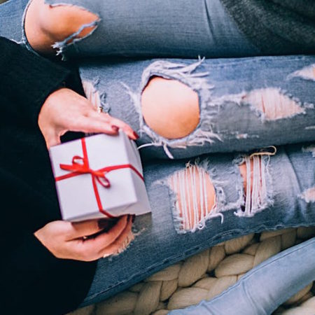 Woman sits with a Christmas present in her lap