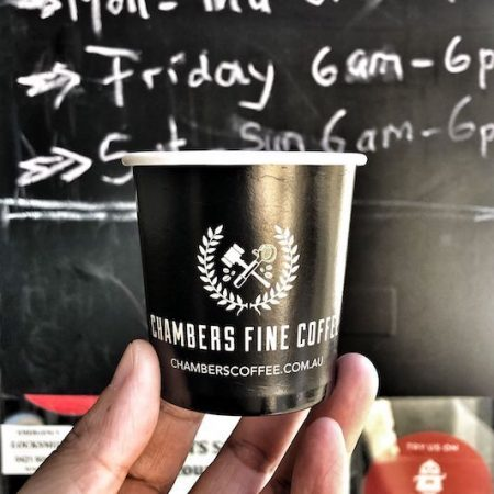 Holding a cup of coffee in front of the trading hours of Chambers Fine Coffee
