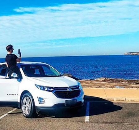 James Banham standing in a Holden Equinox SUV car to take a picture of the ocean