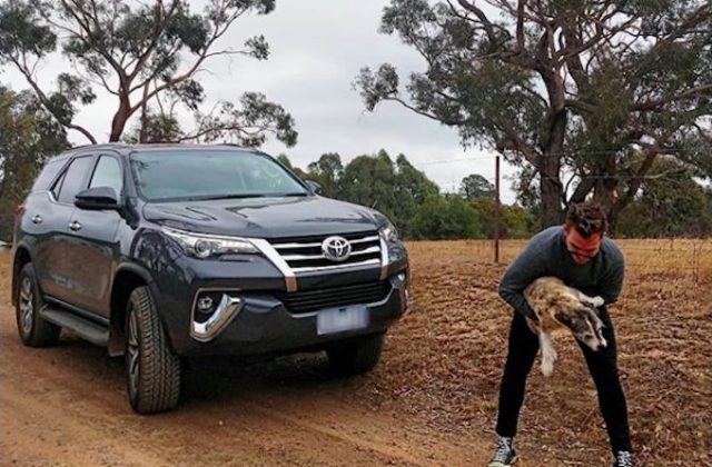 James Banham playing with a dog next to the Toyota Fortuner